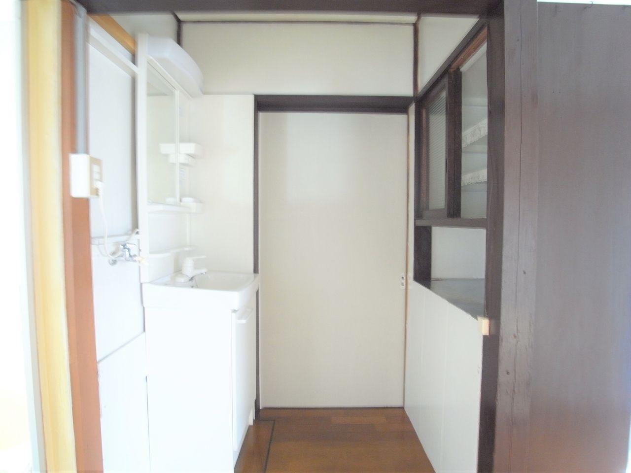手前には食器棚と洗面台が向かい合っています